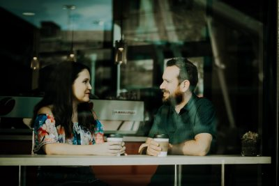 Man and woman having coffee at a coffee shop in the front window smiling and talking